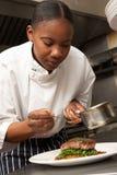 Cocinero que agrega la salsa al plato en cocina del restaurante imagenes de archivo