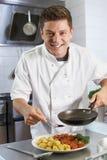 Cocinero que agrega la salsa al plato en cocina del restaurante fotografía de archivo