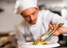 Cocinero que arregla la ensalada lanzada en un cuenco blanco Fotografía de archivo
