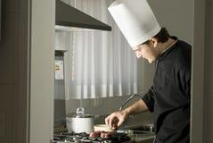 Cocinero que asa a la parilla los filetes imagenes de archivo