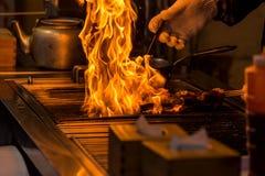 cocinero que asa a la parrilla el Bbq con la llama de la quema en restaurante Fotos de archivo