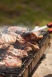 Cocinero que asa a la parrilla el filete del cerdo en la llama Imagen de archivo libre de regalías