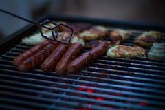 Cocinero que asa a la parrilla la salchicha en la llama Foto de archivo libre de regalías