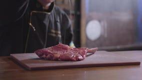 Cocinero que asperja la sal y la pimienta en el pedazo crudo de costillas de la carne adobadas y listas para ser frito en parrill almacen de video