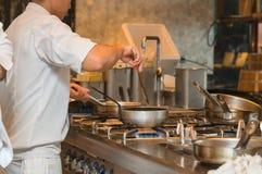 Cocinero que cocina con la cacerola en la cocina Foto de archivo