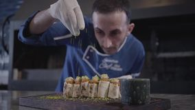 Cocinero que cocina el plato sabroso en cierre moderno del restaurante para arriba Hombre en uniforme del cocinero que asperja ke almacen de metraje de vídeo