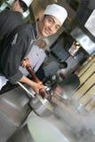 Cocinero que cocina en la cena Foto de archivo libre de regalías
