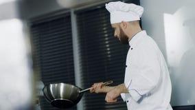 Cocinero que cocina en wok en el restaurante de la cocina Cocinero del hombre que prepara la comida asiática en cacerola metrajes