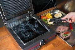 Cocinero que cocina la carne y verduras en una parrilla foto de archivo