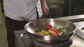 Cocinero que cocina la comida en cocina almacen de video