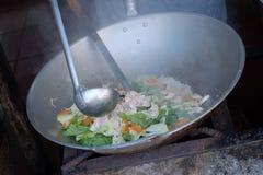 cocinero que cocina la isleta del casquillo el t?rmino Hokkien-derivado para un indonesio chino popular sofrito imagenes de archivo