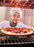Cocinero que cocina la pizza en el horno Foto de archivo libre de regalías