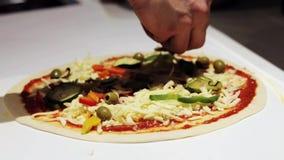 Cocinero que cocina la pizza en la pizzería metrajes