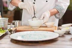 Cocinero que cocina un plato en la cocina Fotos de archivo