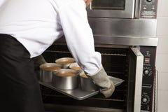 Cocinero que coloca las tortas en el horno Fotografía de archivo libre de regalías