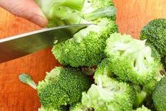 Cocinero que corta el bróculi verde fresco para cocinar Acción para arriba en la comida del invierno Imagen de archivo libre de regalías