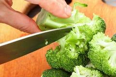 Cocinero que corta el bróculi verde fresco para cocinar Acción para arriba en la comida del invierno Imagenes de archivo