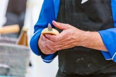 Cocinero que corta el pan fresco para la hamburguesa fotografía de archivo