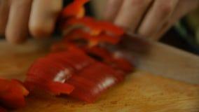 Cocinero que corta el paprika rojo almacen de metraje de vídeo