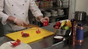 Cocinero que corta el paprika rojo, tiro medio metrajes