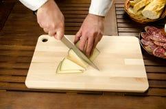 Cocinero que corta el queso, detalle de las manos Foto de archivo libre de regalías