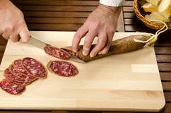 Cocinero que corta el salami, detalle de las manos Imagen de archivo libre de regalías