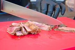 Cocinero que corta la carne asada a la parrilla Imágenes de archivo libres de regalías