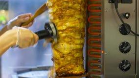 Cocinero que corta la carne del doner del escupitajo en la tienda del kebab