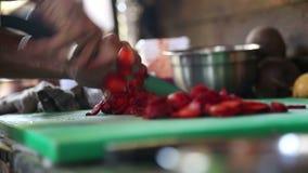Cocinero que corta las fresas con un cuchillo en una tajadera verde almacen de metraje de vídeo