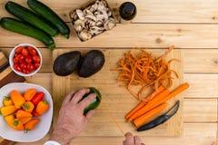 Cocinero que corta las verduras frescas para cocinar Foto de archivo libre de regalías