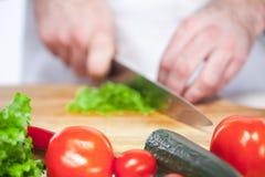 Cocinero que corta una lechuga verde su cocina Imagen de archivo libre de regalías