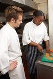 Cocinero que da instrucciones al aprendiz en cocina del restaurante fotos de archivo libres de regalías