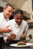 Cocinero que da instrucciones al aprendiz en cocina del restaurante Imágenes de archivo libres de regalías