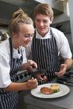 Cocinero que da instrucciones al aprendiz en cocina del restaurante Imagen de archivo