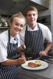 Cocinero que da instrucciones al aprendiz en cocina del restaurante fotografía de archivo