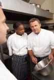 Cocinero que da instrucciones a aprendices imagen de archivo