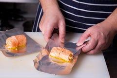 Cocinero que envuelve para arriba los rollos de los salmones Fotos de archivo