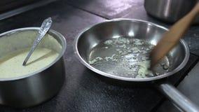 Cocinero que fríe el ajo en la cacerola metrajes