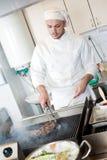 Cocinero que fríe el filete de carne de vaca en parrilla Fotografía de archivo libre de regalías