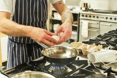 Cocinero que fríe los huevos Imágenes de archivo libres de regalías