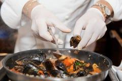 Cocinero que fríe los mejillones Fotos de archivo libres de regalías