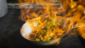 Cocinero que fríe vehículos El coñac se enciende en la cacerola Abra el fuego en la cocina