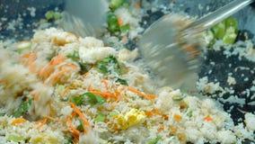 Cocinero que fríe verduras y el arroz metrajes