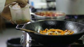 Cocinero que fríe verduras y la carne en un wok en la cocina almacen de video