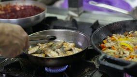 Cocinero que fríe verduras y la carne en un wok en la cocina metrajes