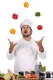 Cocinero que hace juegos malabares con pimientas Fotografía de archivo libre de regalías