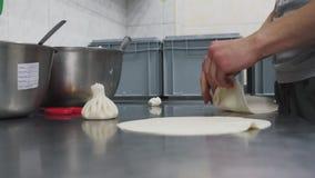 Cocinero que hace khinkali con cierre del requesón para arriba Cocina georgiana Preparación de comida en restaurante moderno past almacen de video