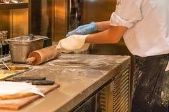 Cocinero que hace la pizza en cocina del restaurante imagen de archivo