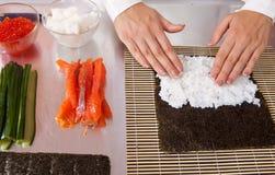 Cocinero que hace los rodillos de sushi Foto de archivo