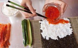 Cocinero que hace los rodillos de sushi con el caviar Foto de archivo